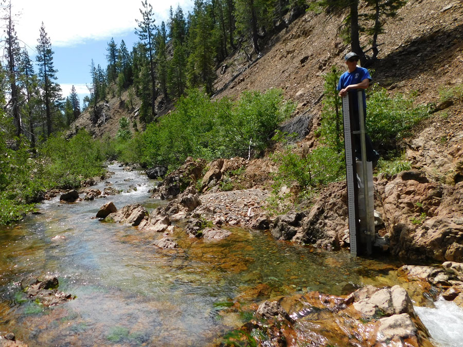 A river in a narrow canyon. A woman works at the top of a high gauge pole.