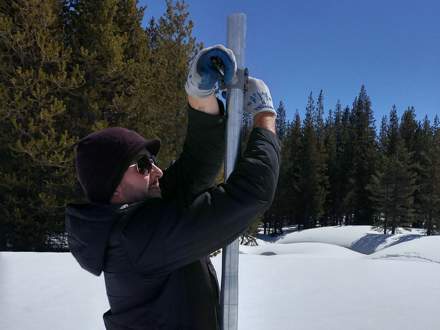 A man in the snow measures snow-water content.