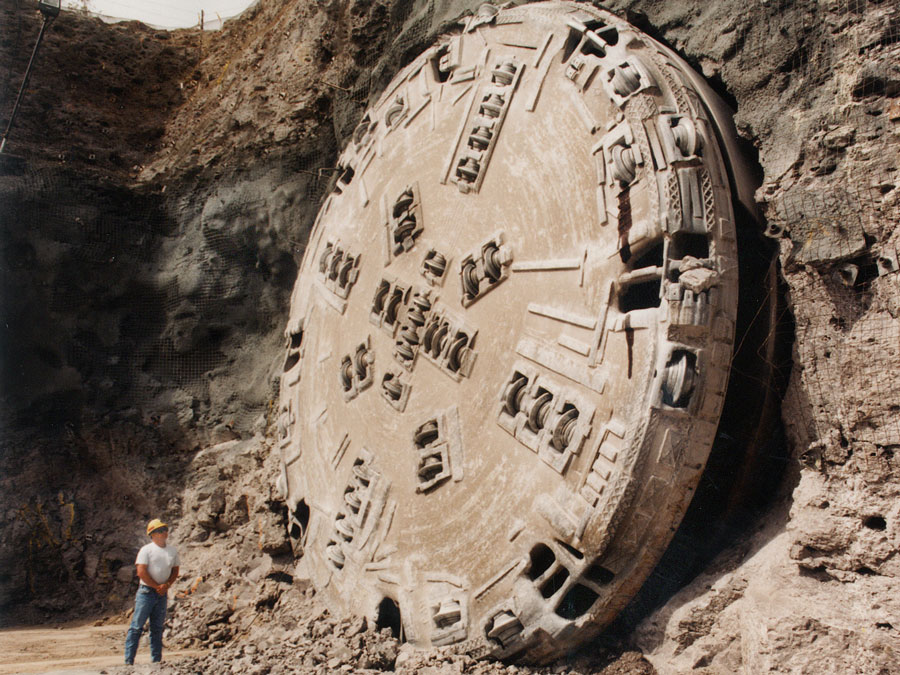The circular end of a tunnel boring machine is more than four times the height of a man standing next to it.