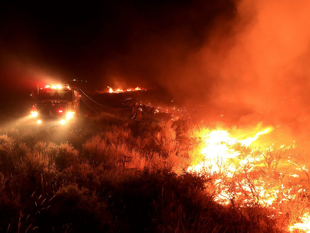 A wildfire burns hot in the Idaho sage brush as several fire fighters spray water hoses from a truck.