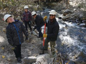 Several children and a man, all wearing safety helmets, by a creek.