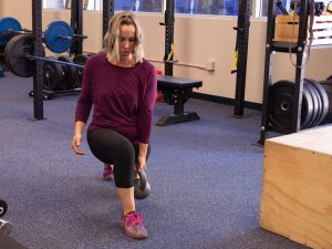Woman with blond hair wearing a purple shirt inside a weight room.