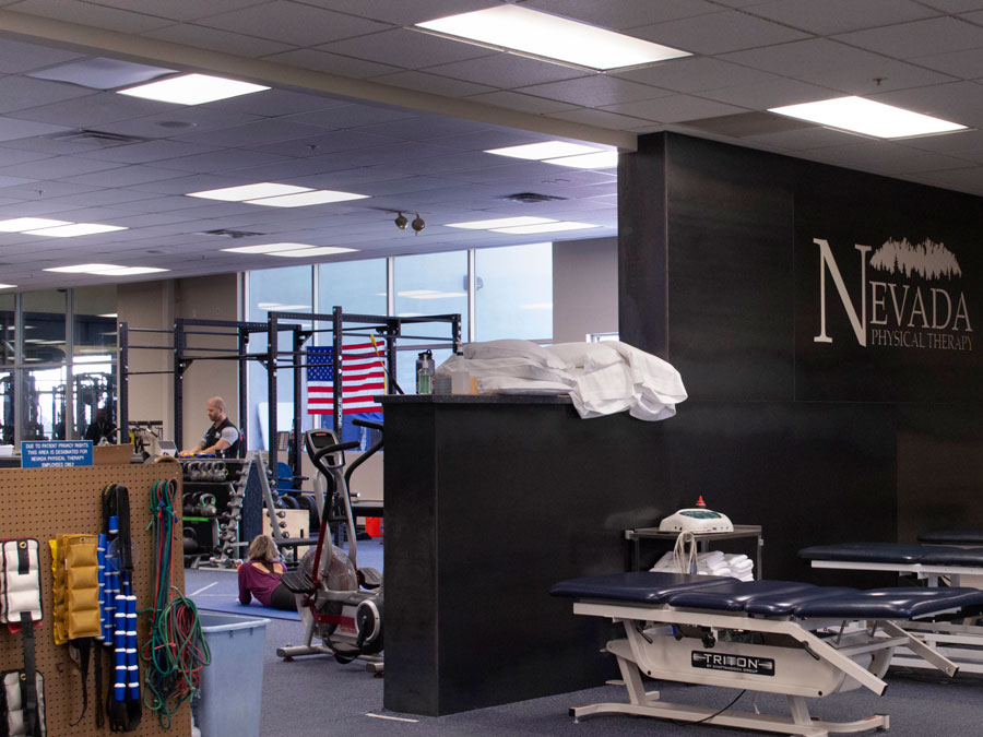 A large room with massage tables on one side of a partial wall and weight equipment on the other side.