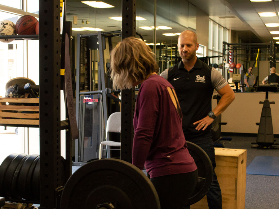 White man in a dark gym suit stands by a blonde woman lifting a weighted barbell.