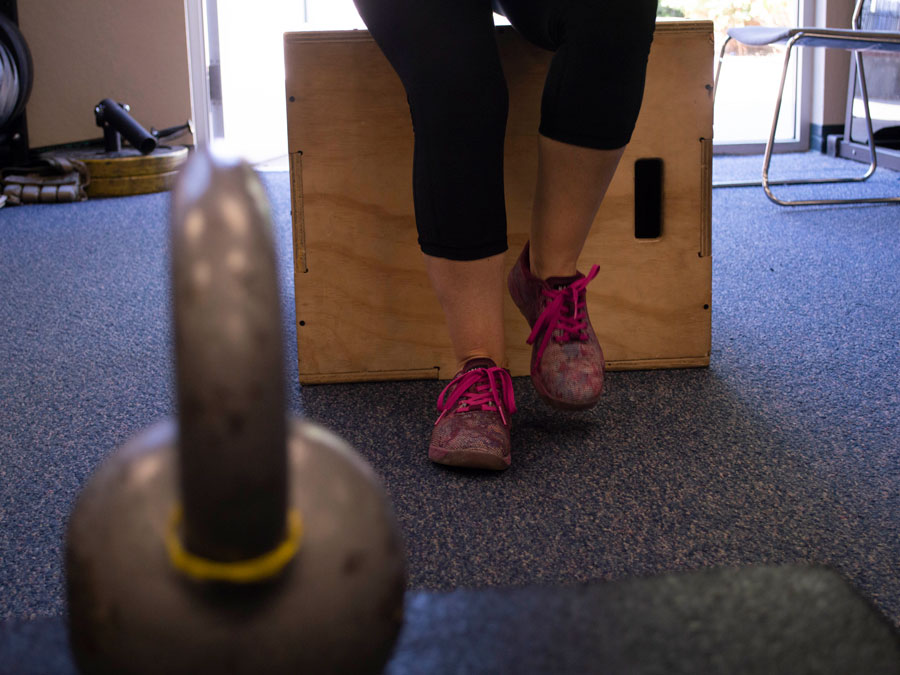 A woman's legs, covered in exercise pants, from the knees down, with purple tennis shoes.