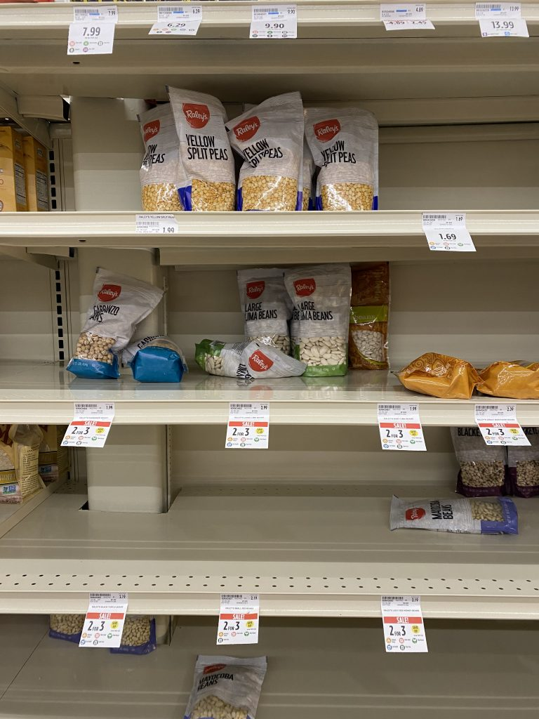 Several nearly empty grocery shelves in the dried bean aisle. Only a few lima beans and garbanzo beans are left.