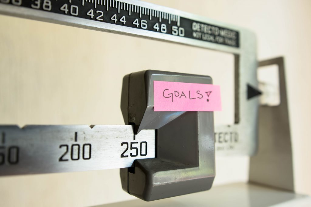 "A physician beam scale has a post-it note labeled ""goals"" taped to it."