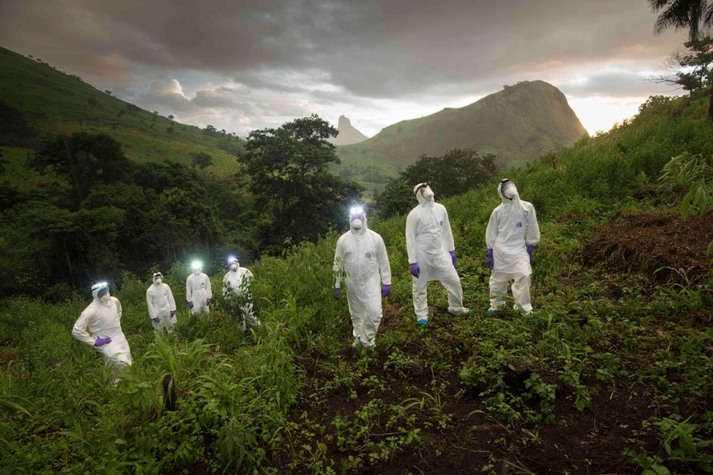 Researchers wearing all-white protective gear pose on a green hillside in Sierra Leone.
