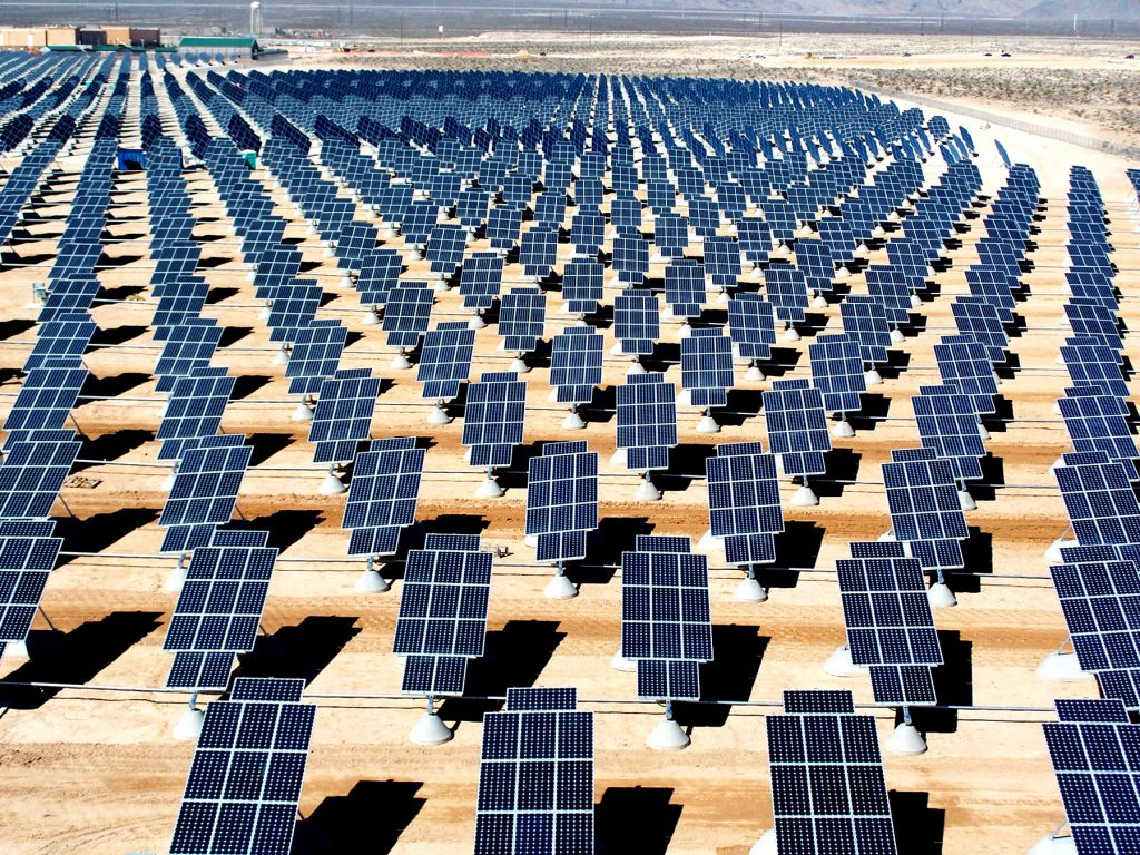 Rectangular solar panels, each standing on its own short pedestal, in a flat, arid landscape.