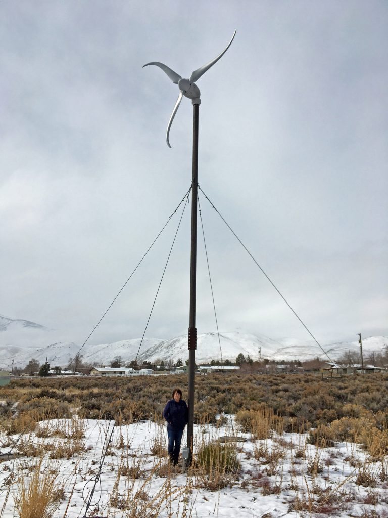 A woman standing beneath a thirty-four foot tall wind turbine.