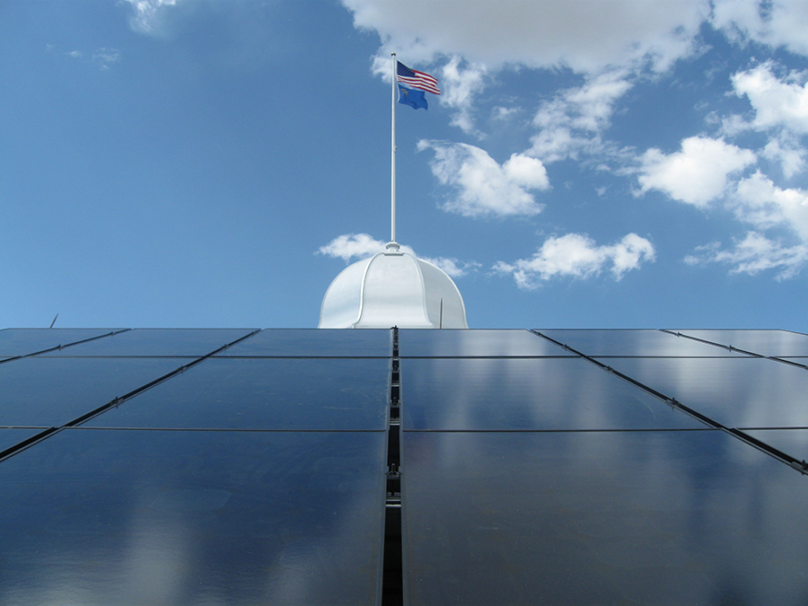 Shiny blue-gray panels slope up toward a white cupola, topped by a flagpole with the Nevada and American flags, against a cloud-studded sky.