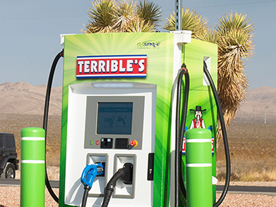 "A chartreuse-green box-shaped charging station with two cords. The sign reads ""terrible's."" Yucca trees in background."