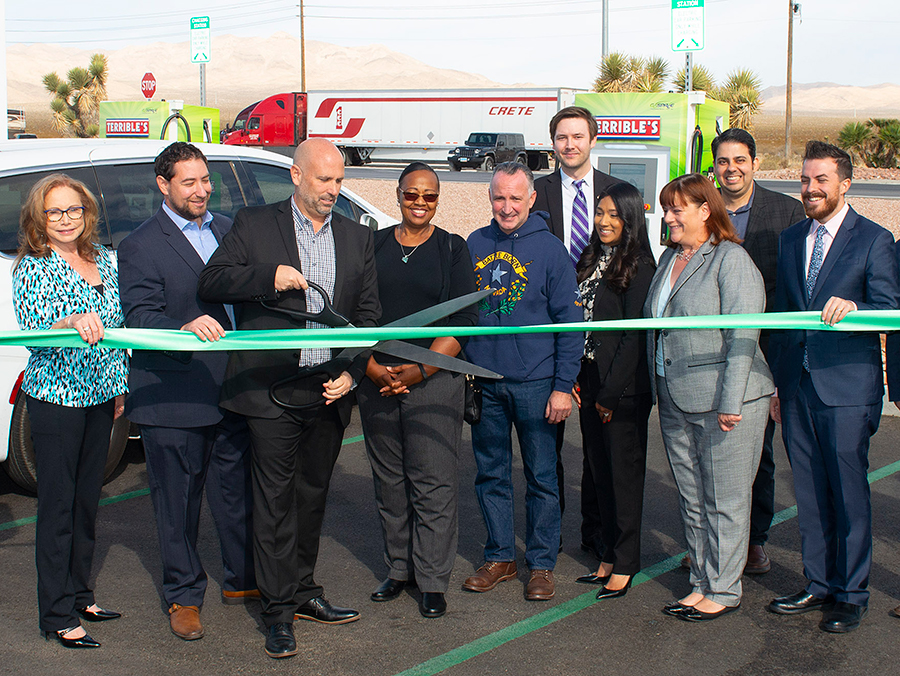 A ribbon-cutting ceremony with 13 people standing in front of a Terrible Herbst EV charging station, with a dry mountain landscape behind them.