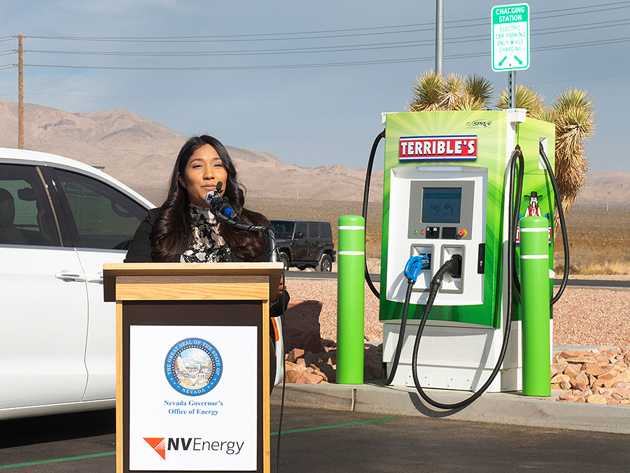 A brown-skinned woman with long black hair stands behind a podium that reads NV Energy. Behind her, a green EV charging station with two cords reads Terrible's.