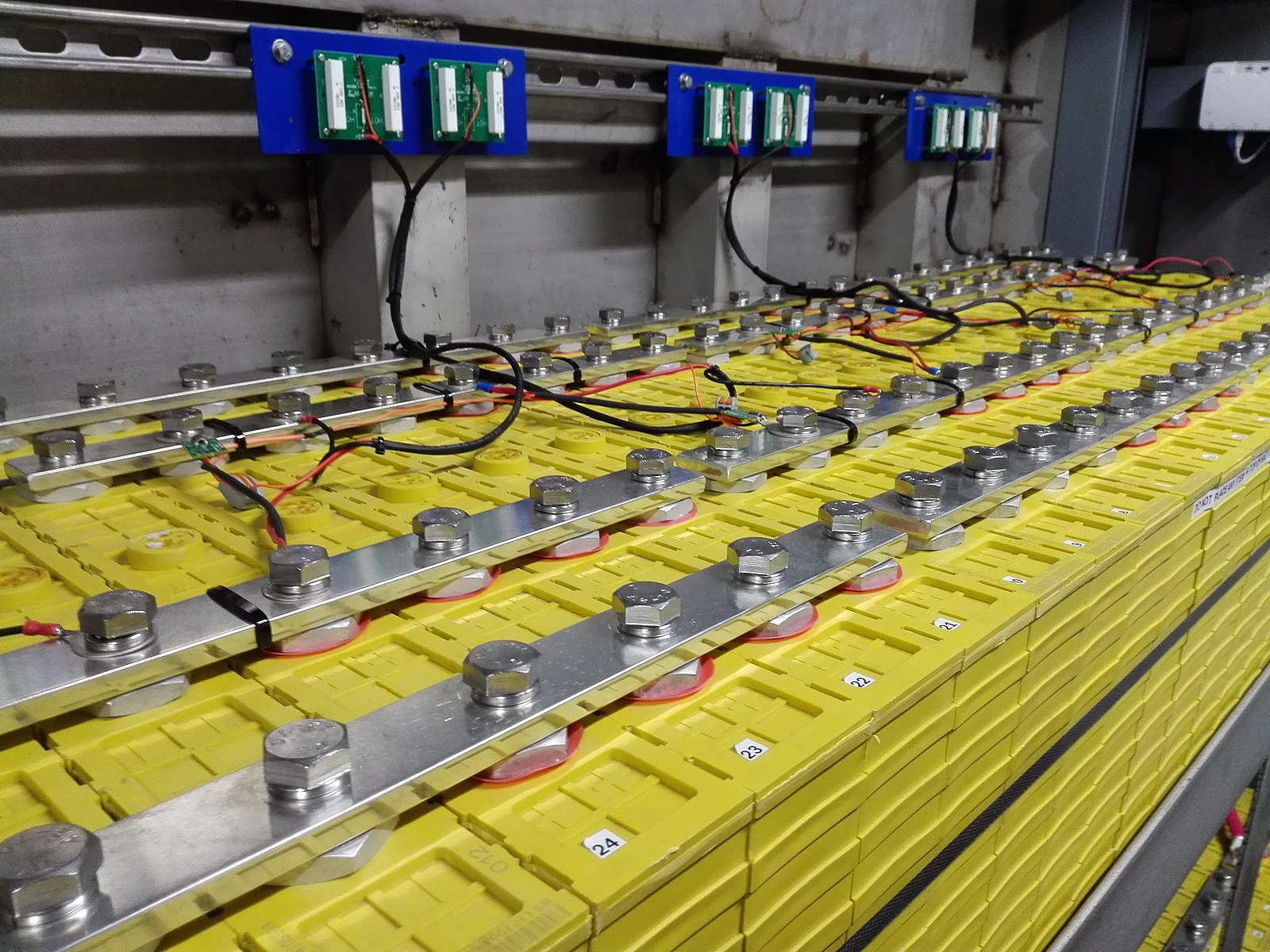 Dozens of large, yellow lithium-ion batteries are bolted together. They are being charged by solar power.