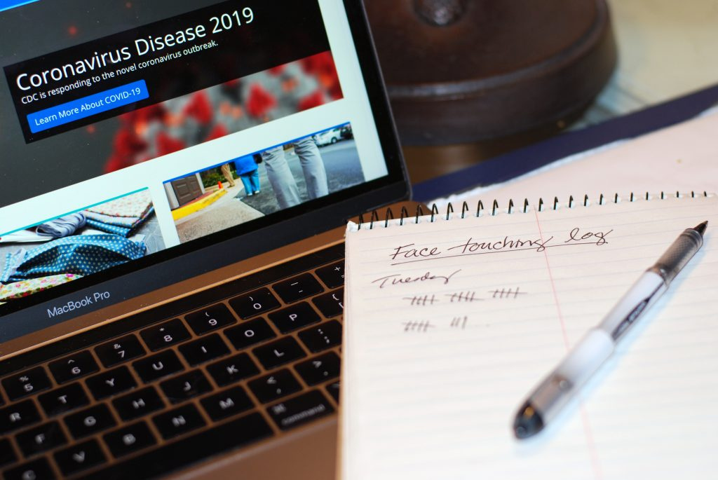 "A pad of paper with a pen situated on it displays log of ""Face Touching"". A laptop screen is displayed in the background with information on the Coronavirus Disease 2019."