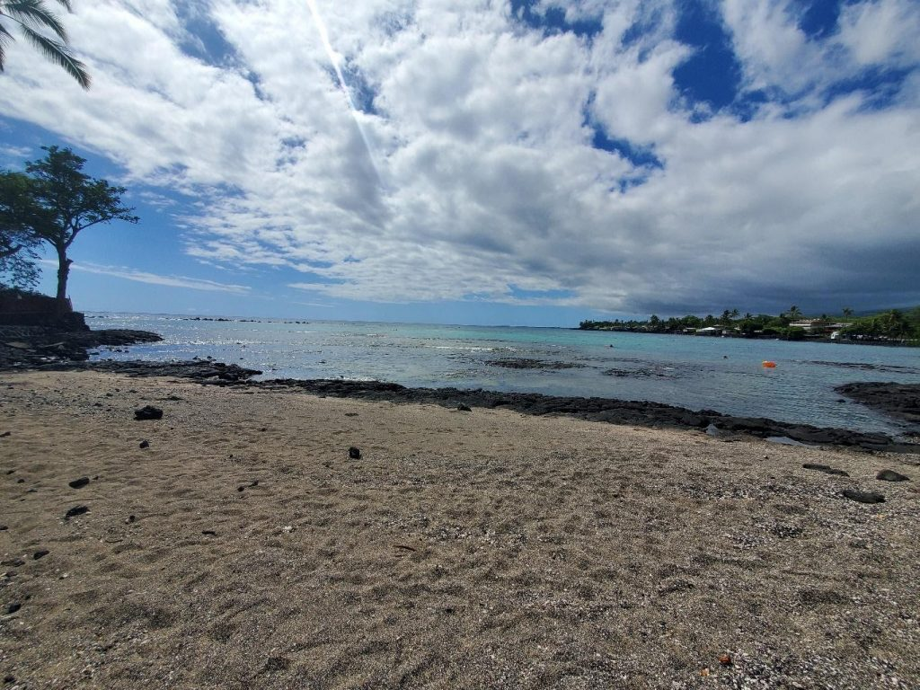 Photo of the beach at Kahaluu Bay. The beach is completely vacant.