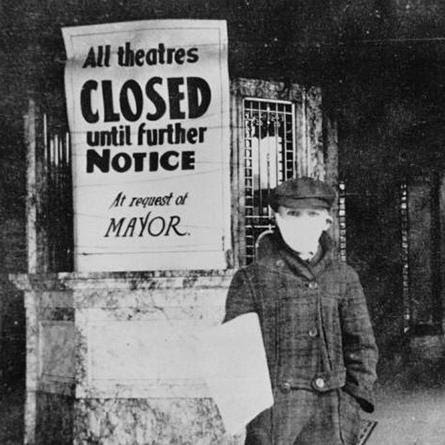 "A person wearing a surgical mask stands next to a sign stating, ""All theatres closed until further notice at request of mayor"""