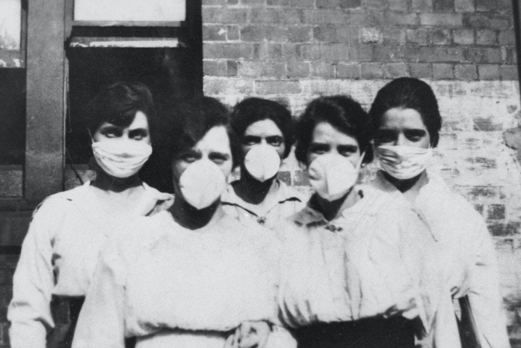 Five women pose wearing face masks. It is a black and white photo, which suggests it was taken during the Spanish Flu pandemic.