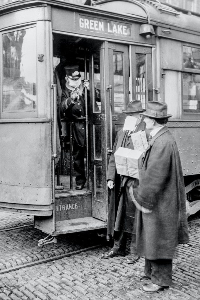 A train conductor wearing a mask speaks with two men - one of whom is wearing a mask, the other is not.