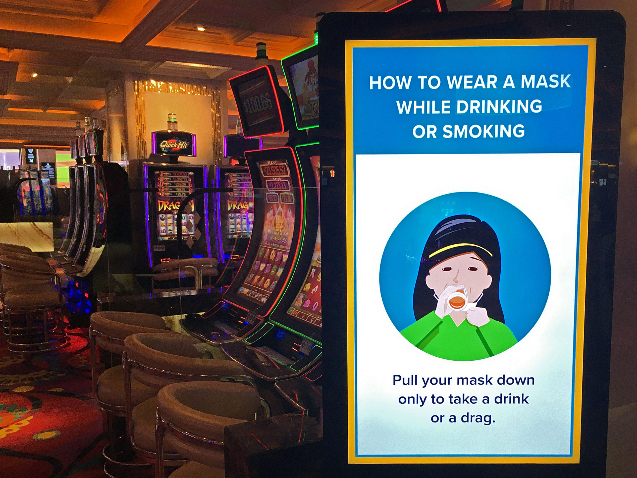 The inside of a glittery casino row of gambling machines and a sign instructing patrons to wear a mask.