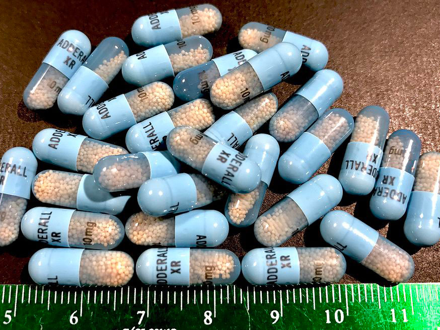 A pile of Adderall pills on the table.