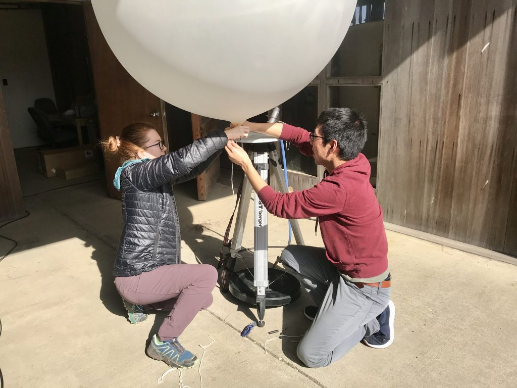 Research Ava Cooper and a teammate work on setting up a weather balloon, which is about a meter in diameter.
