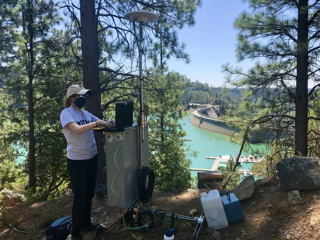 Ava Cooper works on a large piece of equipment with a dam and reservoir in the background.