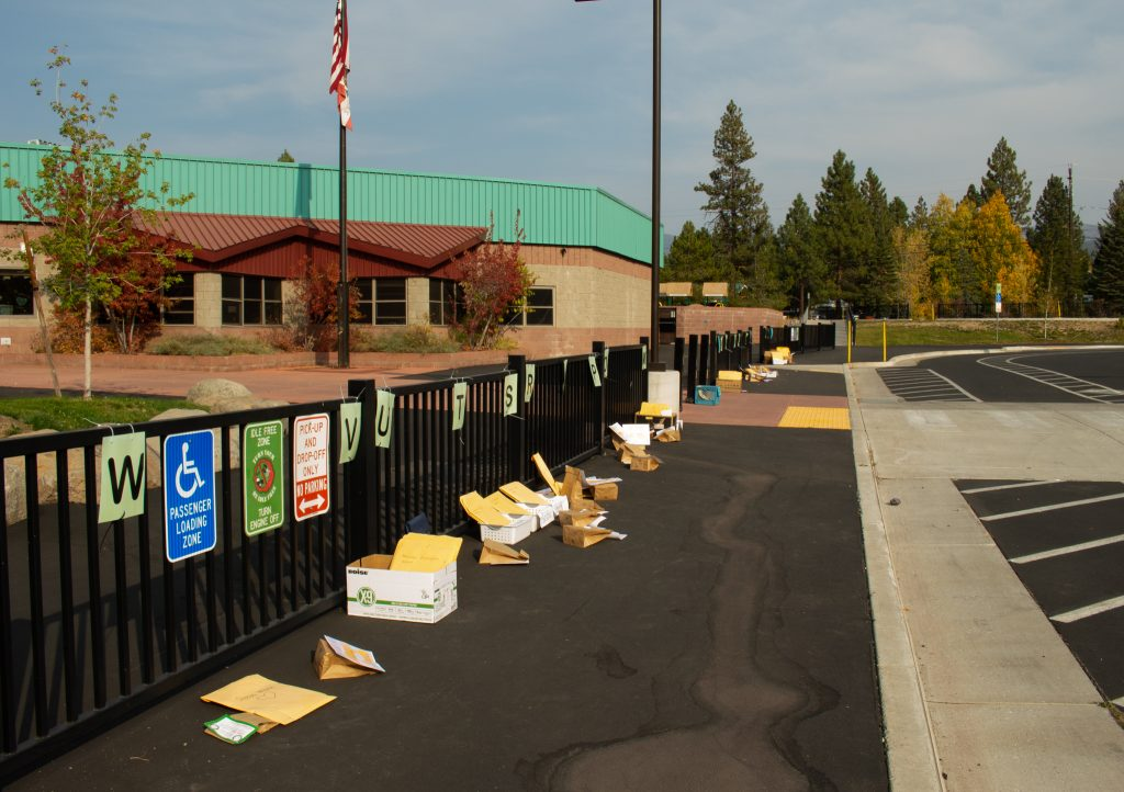 A fence in front of an elementary school has school supplies dropped off in front of it