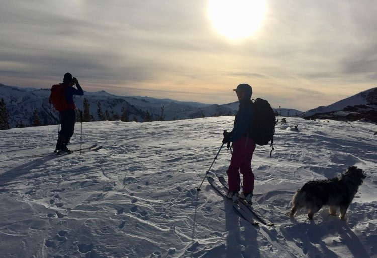 Two skiers and a dog stand in front of a Montana mountain landscape