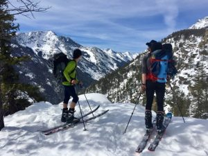 Two skiers with skins on their skis stand in front of a Montana mountain landscape