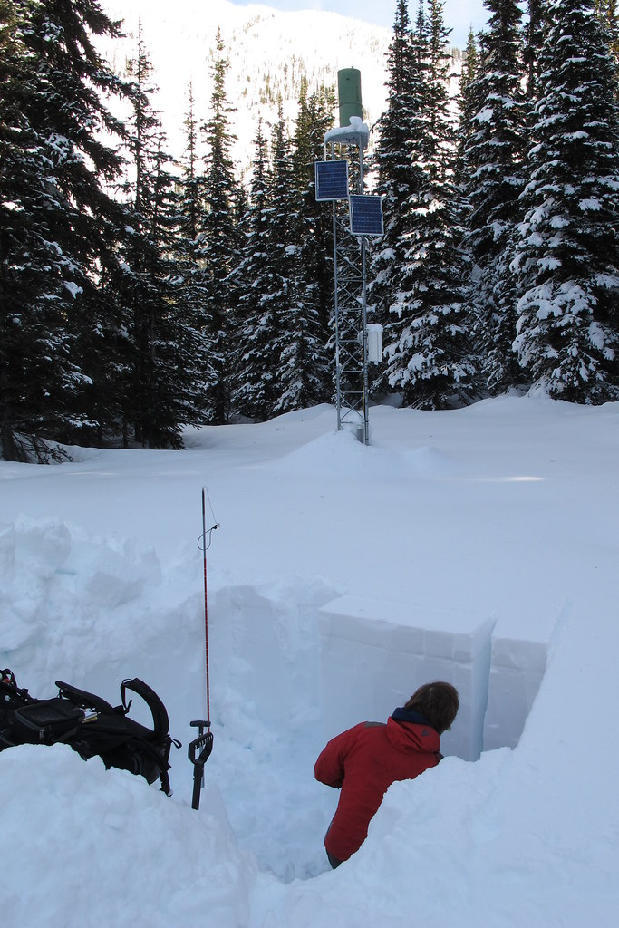 A person sits in a snow pit dug out to check avalanche conditions