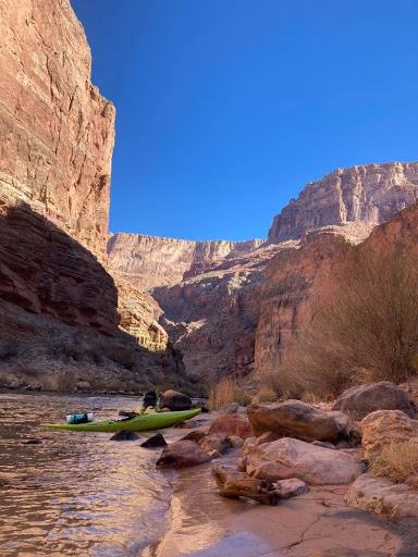 A kayak sits on a beach of the Colorado River in the Grand Canyon.