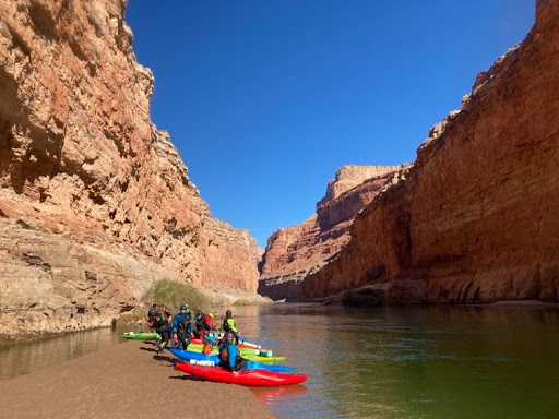 Lots of kayaks sit on a beach in the Grand Canyon