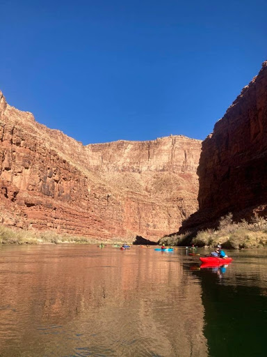 Kayakers paddle through a flat river in the Grand Canyon