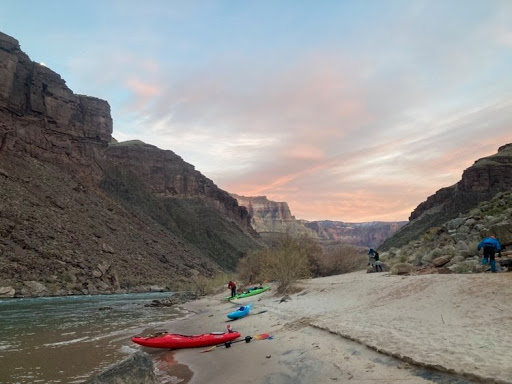 A red kayak sits on a beach in the Grand Canyon under an orange sunset
