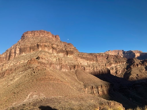 Grand Canyon walls with a small moon in the sky.