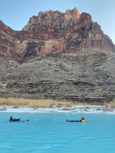 Two people swim in bright blue water with Grand Canyon walls in the background.