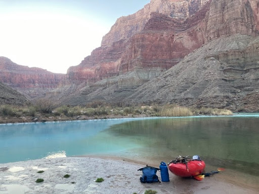 A red boat sits on a beach in front of the confluence of the Little Colorado River and the Colorado River. The Little Colorado River is blue in color from travertine deposits in the water, and it is meeting with the greenish color of the Colorado River. The giant walls of the Grand Canyon are in the background.