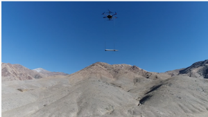 A large drone flies over Nevada mountains carrying magnetic sensing equipment that can identify geological areas that may contain geothermal systems.