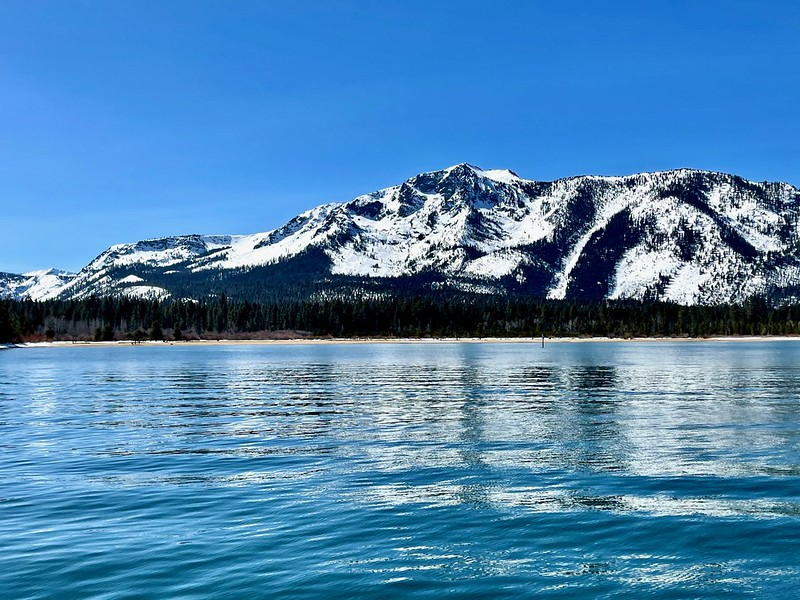 A picture of Lake Tahoe with snow-topped mountains in the background.