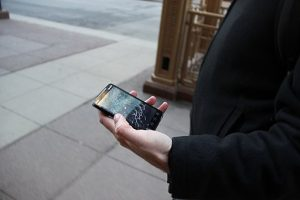 A person holding a smartphone with a broken screen